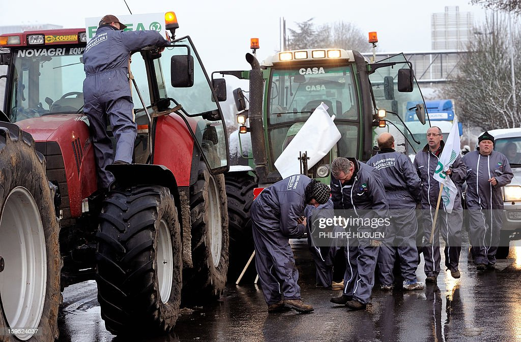 Farmers prepare boards as they organize a partial blockade with some hundred tractors during a demonstration called by farmers local union FDSEA in Arras, northern france, on January 15, 2013. They denounce all kinds of pressure affecting their activities with a slogan :'Laissez-nous travailler' (Let us work).