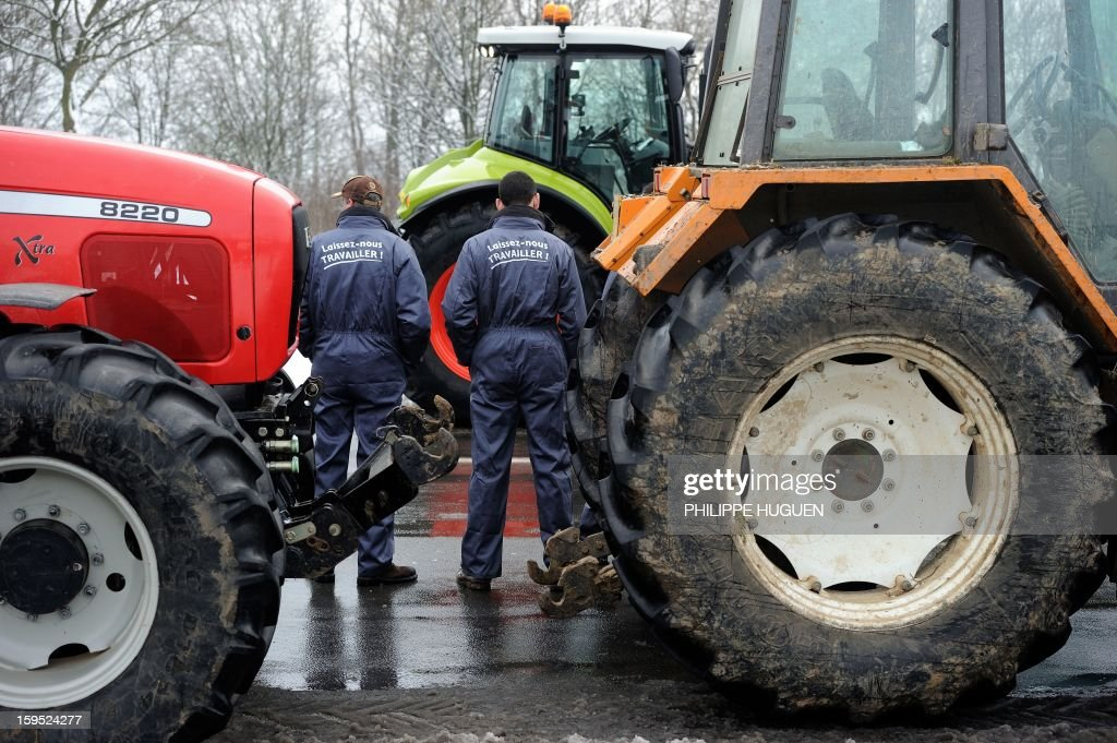'Laissez-nous travailler' (Let us work) on their coveralls as they organize a partial blockade with some hundred tractors during a demonstration called by farmers local union FDSEA in Arras, northern france, on January 15, 2013. They denounce all kinds of pressure affecting their activities. AFP PHOTO PHILIPPE HUGUEN