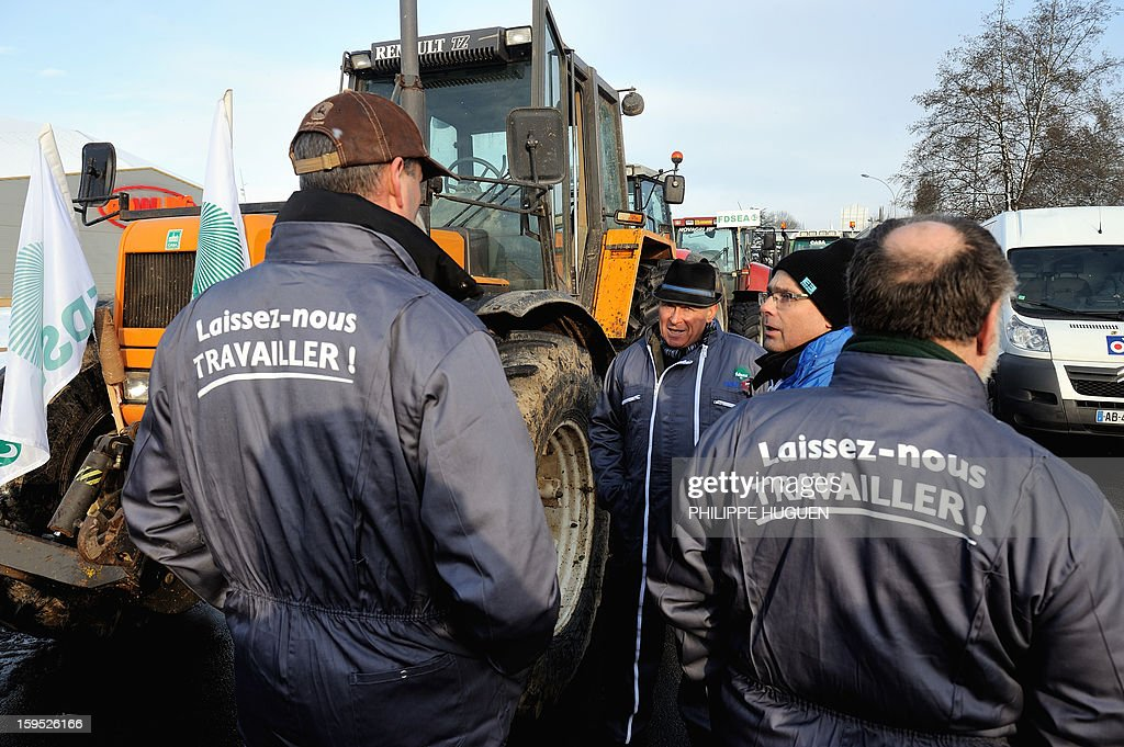 'Laissez-nous travailler' (Let us work) on their coveralls as they organize a partial blockade with some hundred tractors during a demonstration called by farmers local union FDSEA in Arras, northern france, on January 15, 2013. They denounce all kinds of pressure affecting their activities with