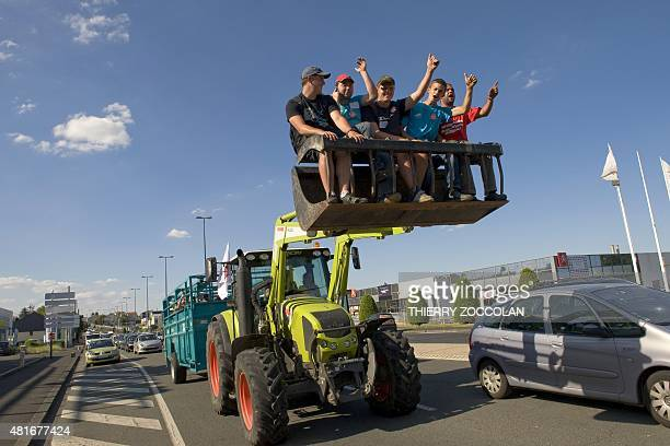 Farmers ride the road shovel attachment of a tractor as they block a road in ClermontFerrand on July 23 as part of a strike against the market prices...