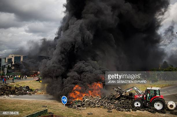 Farmers set tires ablaze in front of a dairy factory of the Lactalis Group in Laval northwestern France during a demonstration against falling food...