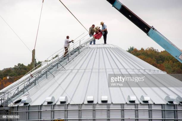 Farmer's setting up steel grain silo for harvest in Dalmatia Pennsylvania USA