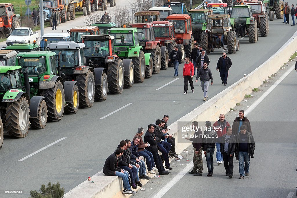 Farmers sit and walk on 29 January, 2013 near their parked tractors near Nikaia, some 380 kms north of Athens and one km before the highway linking Thessaloniki to Athens, to protest against the way they are taxeed. Protesting farmers moved their tractors near the highway, threatening to block traffic on Greece's north-south axis, before being cleared by riot police.