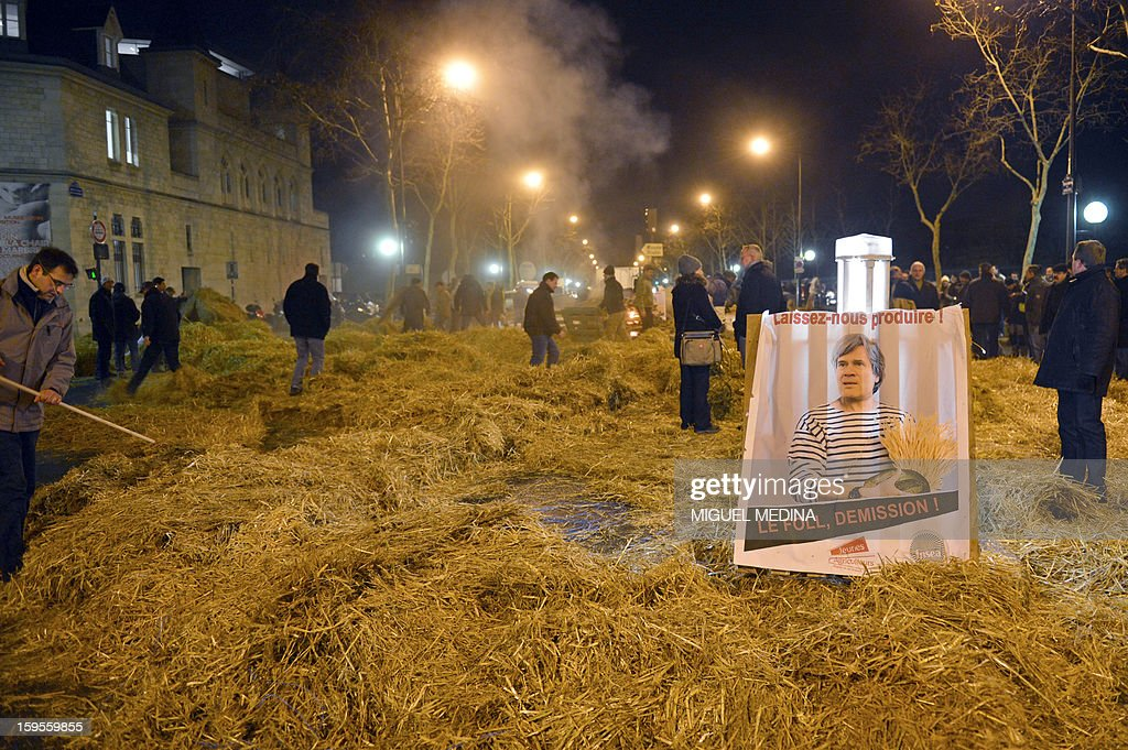 Farmers spread straw on the pavement, early on January 16, 2013 in Paris, near the Agriculture ministry and the Prime Minister official residence, the Hotel Matignon, during a protest called by farmers union FNSEA against new constraints arising from the applications of European Union rules against nitrates. A new map identifies 'vulnerable areas' to nitrates which require special protection to not pollute water resources. The board reads 'Let us produce' and asks for the resignation of Agriculture minister Stephane Le Foll.
