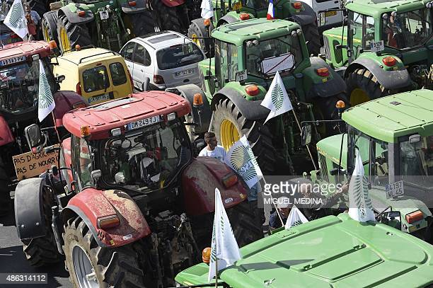 Farmers stand by tractors while staging a national demonstration on September 3 2015 near Place de la Nation in Paris to protest against the falling...