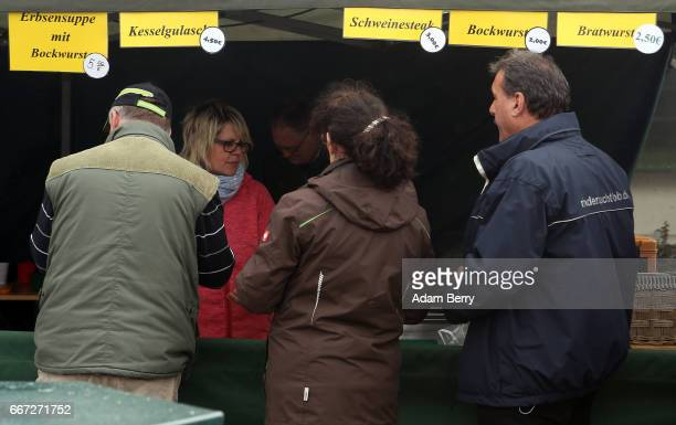 Farmers stand in a line to eat pig and beef products during an annual heifer auction on April 11 2017 in Gross Kreutz Germany Around 80 Angus...