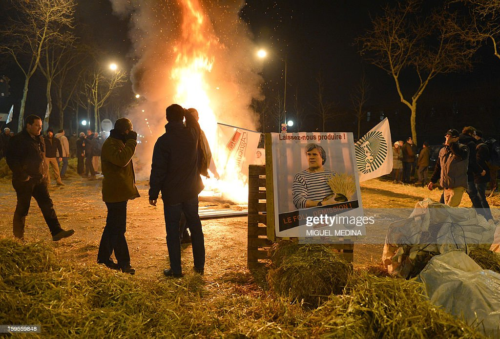 Farmers stand near fire they lighted with straw and wooden pallets, early on January 16, 2013 in Paris, near the Agriculture ministry and the Prime Minister official residence, the Hotel Matignon, during a protest called by farmers union FNSEA against new constraints arising from the applications of European Union rules against nitrates. A new map identifies 'vulnerable areas' to nitrates which require special protection to not pollute water resources. The board reads 'Let us produce' and asks for the resignation of Agriculture minister Stephane Le Foll.