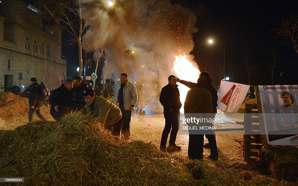 Farmers stand near fire they lighted with straw and wooden pallets, early on January 16, 2013 in Paris, near the Agriculture ministry and the Prime Minister official residence, the Hotel Matignon, during a protest called by farmers local union FDSEA against new constraints arising from the applications of European Union rules against nitrates. A new map identifies 'vulnerable areas' to nitrates which require special protection to not pollute water resources. The board at right reads 'Let us produce' and asks for the resignation of Agriculture Minister Stephane Le Foll. AFP PHOTO MIGUEL MEDINA