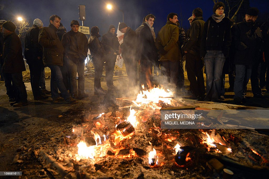 Farmers stand near fire they lighted with straw and wooden pallets, early on January 16, 2013 in Paris, near the Agriculture ministry and the Prime Minister official residence, the Hotel Matignon, during a protest called by farmers union FNSEA against new constraints arising from the applications of European Union rules against nitrates. A new map identifies 'vulnerable areas' to nitrates which require special protection to not pollute water resources. AFP PHOTO MIGUEL MEDINA