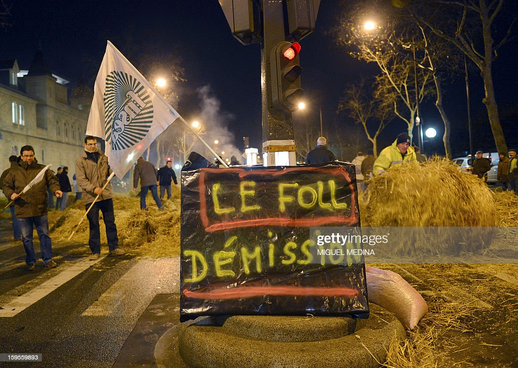 Farmers stand near straw they spread early on January 16, 2013 in Paris, near the Agriculture ministry and the Prime Minister official residence, the Hotel Matignon, during a protest called by farmers union FNSEA against new constraints arising from the applications of European Union rules against nitrates. A new map identifies 'vulnerable areas' to nitrates which require special protection to not pollute water resources. The boards ask for the resignation of Agriculture Minister Stephane Le Foll.