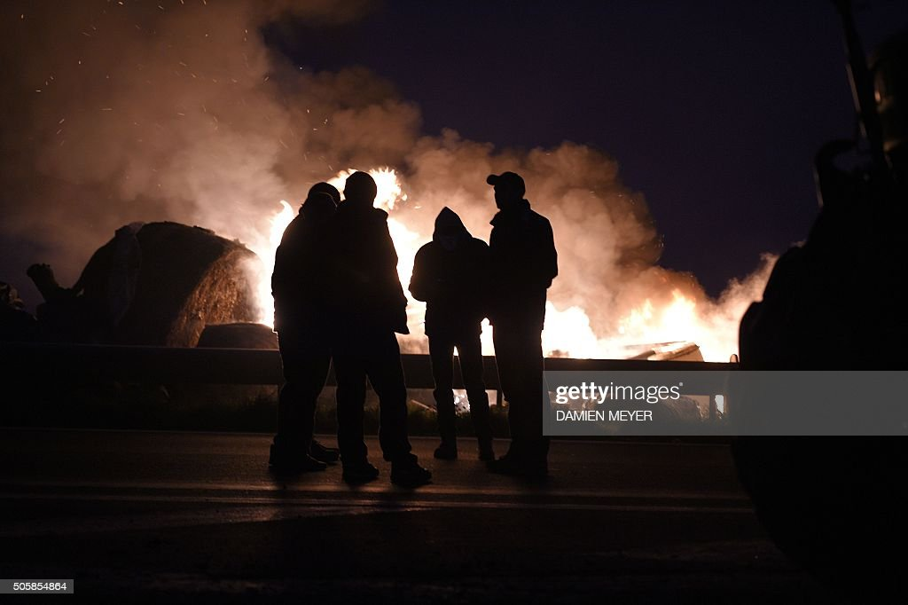 Farmers stand next to burning tires and haystacks on the RN 12 road on January 20 2016 next to Saint Brieuc northwestern France during a...