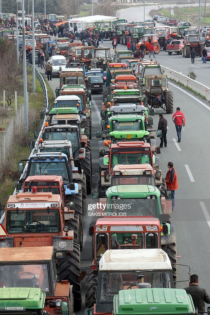 Farmers stand on 29 January, 2013 next to parked tractors near Nikaia, some 380 kms north of Athens and one km before the highway linking Thessaloniki to Athens, to protest against the way they are taxeed. Protesting farmers moved their tractors near the highway, threatening to block traffic on Greece's north-south axis, before being cleared by riot police.