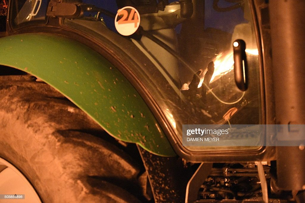 Farmers standing next to burning tires and haystacks reflect in the pane of a tractor on the RN 12 road on January 20 2016 next to Saint Brieuc...