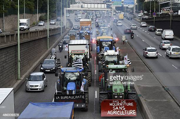 Farmers steering tractors leave Paris by the ring road after taking part in a national demonstration on September 3 to protest against the falling...