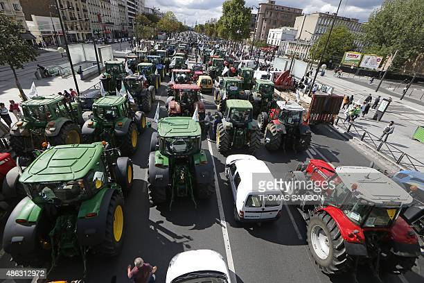 Farmers steering tractors take part in a national demonstration on the Cours de Vincennes avenue near Place de la Nation in Paris on September 3 to...