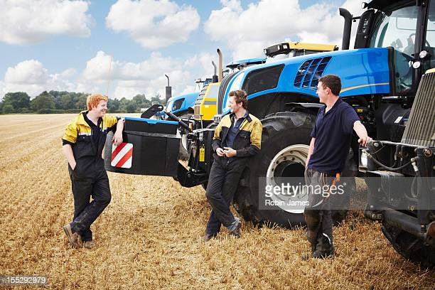 Farmers talking by machinery in field