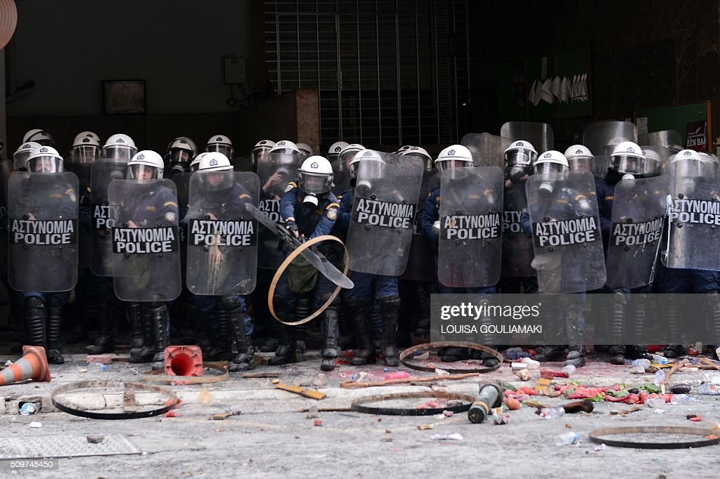 Farmers throw objects at police blocking the entrance to the Agriculture ministry in Athens, during a demonstration against the pension reform on February 12, 2016 Fears that Greece will exit the eurozone, a 'Grexit', could revive if Greek authorities do not come up with 'credible' reforms, notably on pensions, a senior IMF official said February 11, 2016. / AFP / LOUISA GOULIAMAKI