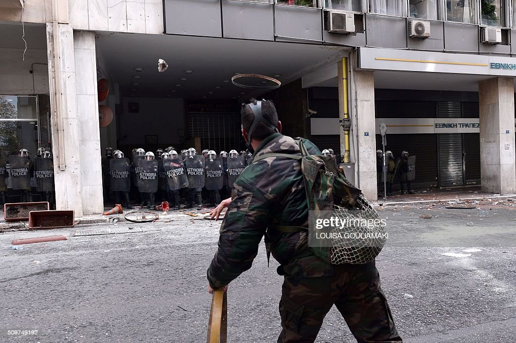 Farmers throw objects towards the Agriculture ministry in Athens during a demonstration against the pension reform on February 12, 2016. Fears that Greece will exit the eurozone, a 'Grexit', could revive if Greek authorities do not come up with 'credible' reforms, notably on pensions, a senior IMF official said February 11, 2016. / AFP / LOUISA GOULIAMAKI