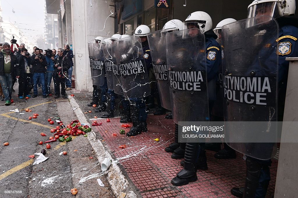 Farmers throw pait and objects at riot police officers blocking the access of the Agriculture ministry during a demonstration against the pension reform on February 12, 2016. Fears that Greece will exit the eurozone, a 'Grexit', could revive if Greek authorities do not come up with 'credible' reforms, notably on pensions, a senior IMF official said February 11, 2016. / AFP / LOUISA GOULIAMAKI