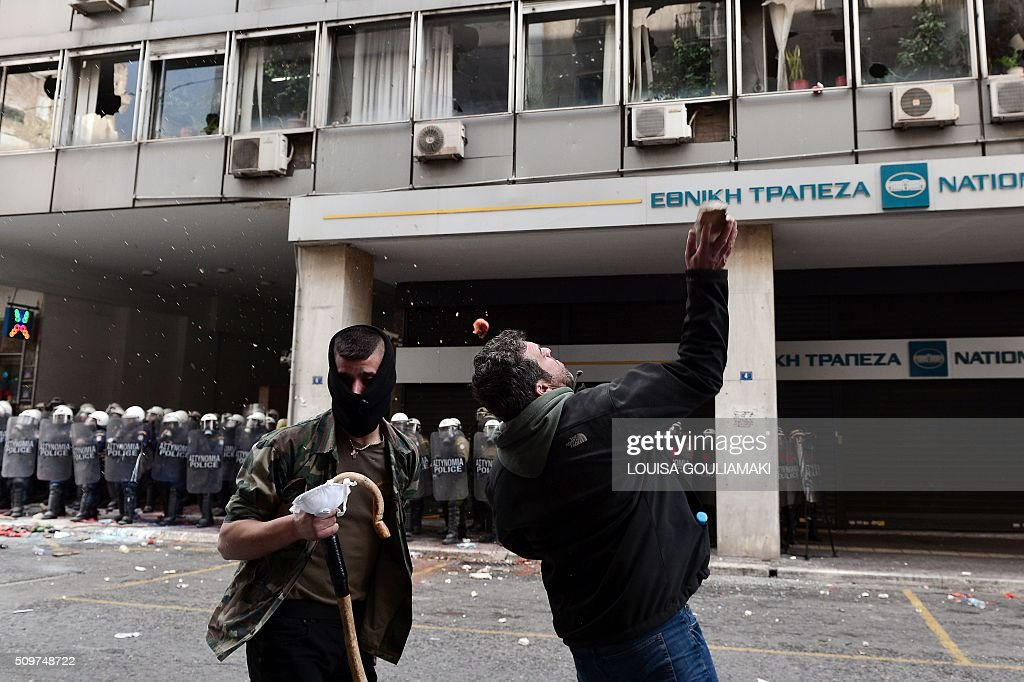 Farmers throw stones to smash windows of the Agriculture ministry in Athens, during a demonstration against pension reform on February 12, 2016. Fears that Greece will exit the eurozone, a 'Grexit', could revive if Greek authorities do not come up with 'credible' reforms, notably on pensions, a senior IMF official said February 11, 2016. / AFP / LOUISA GOULIAMAKI