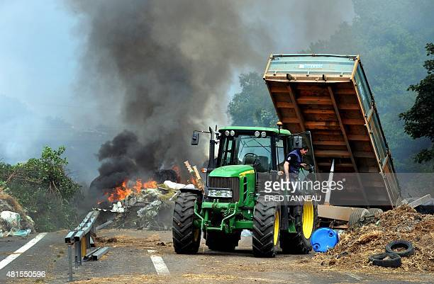 Farmers use a tractor along with burning hay and tyres to block the highway between Morlaix and Brest during a demonstration against the market...
