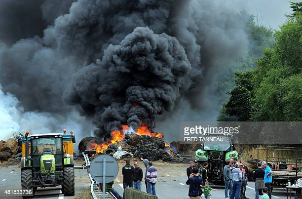 Farmers use tractors and burn tires and hay as they block the highway between Morlaix and Brest during a demonstration against the market prices of...
