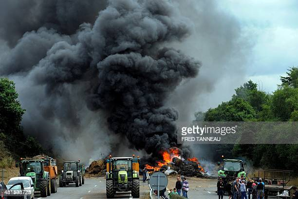 Farmers use tractors and burn tires hay and manure as they block the highway between Morlaix and Brest during a demonstration against the market...