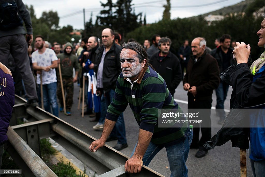 Farmers wait for the highway to open, near in Athens, as police block the road to prevent the farmers to access the centre of Athens with tractors during a protest against pension reform and tax issues on February 12, 2016. Fears that Greece will exit the eurozone, a 'Grexit', could revive if Greek authorities do not come up with 'credible' reforms, notably on pensions, a senior IMF official said February 11, 2016. / AFP / ANGELOS TZORTZINIS