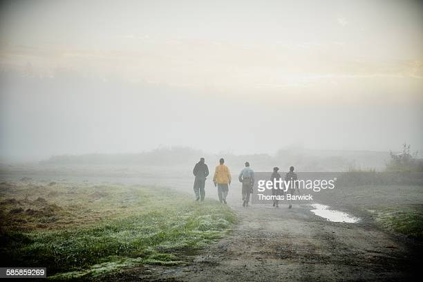 Farmers walking on road to harvest in field