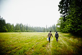 Farmers walking to feed livestock rear view