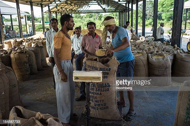 Farmers weigh their soybeans in gunny sacks to be sold at a grain market in Burhanpur Madhya Pradesh India on Friday Oct 19 2012 Global soybean...