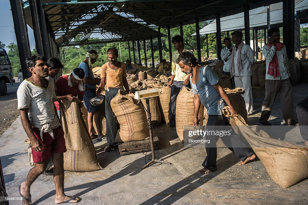 Farmers weigh their soybeans in gunny sacks to be sold at a grain market in Burhanpur, Madhya Pradesh, India, on Friday, Oct. 19, 2012. Global soybean consumption will drop about 3 million metric tons in 2012-2013 as record prices curb demand for the oil made from the oilseed for food and biofuel, Thomas Mielke, executive director of Oil World, said. Photographer: Sanjit Das/Bloomberg via Getty Images