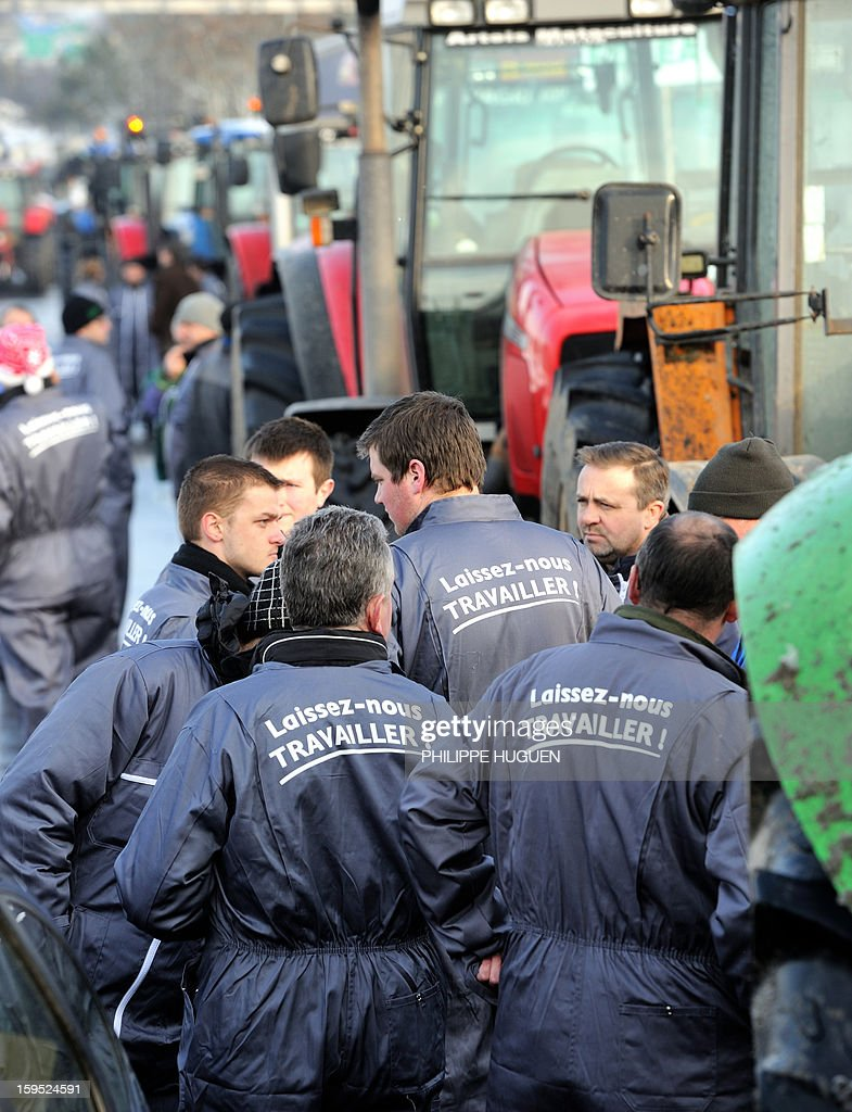 'Laissez-nous travailler' (Let us work) on their coveralls, are gathered during the partial blockade they organized with some hundred tractors during a demonstration called by farmers local union FDSEA in Arras, northern france, on January 15, 2013. They denounce all kinds of pressure affecting their activities.