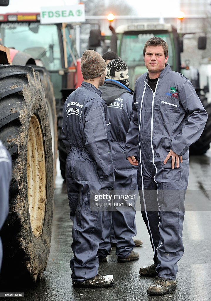 'Laissez-nous travailler' (Let us work) on their coveralls, sspeak together as they organize a partial blockade with some hundred tractors during a demonstration called by farmers local union FDSEA in Arras, northern france, on January 15, 2013. They denounce all kinds of pressure affecting their activities.