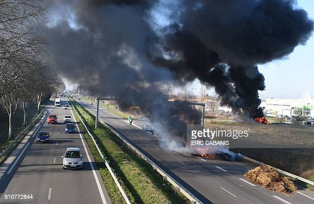 TOPSHOT Farmers with tractors burn bales of hay block at the access to a hypermarket in the Toulouse area in RoquessurGaronne as they protest against...