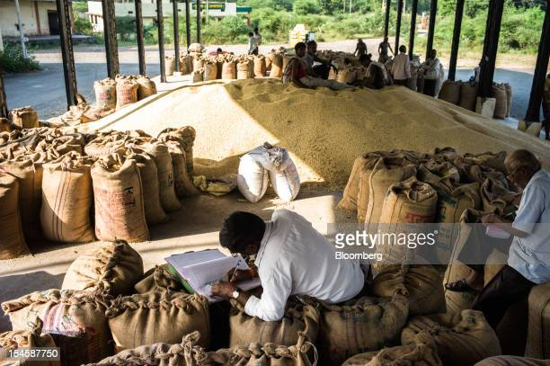 Farmers write in their log books as they wait to sell their soybeans at a grain market in Burhanpur Madhya Pradesh India on Friday Oct 19 2012 Global...