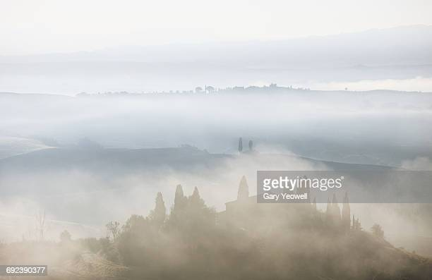 Farmhouse in misty Tuscan landscape at dawn