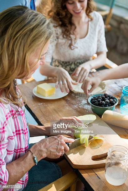 Farmhouse in the country in New York State. Four generations of women in a family baking cookies and apple pie.