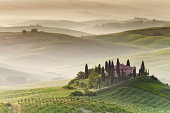 Picturesque and idyllic view on farmhouse at sunrise near Pienza and San Quirico d´Orcia in Tuscany, Italy. Morning fog and haze between hills are very common in spring.