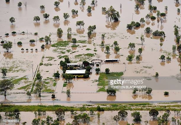 A farmhouse is surrounded by water after the swollen Fitzroy River broke its banks and flooded the city of Rockhampton and surrounding farmland on...