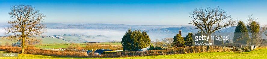 Farmhouse overlooking misty valley