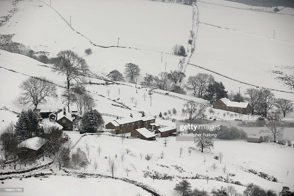 Farmhouses are surrounded by snow in the Peak District on January 21, 2013 in Macclesfield, United Kingdom. The Met Office has issued a red weather warning for parts of the Uk and advising against all non-essential travel as up to 30cm of snow is expected to fall in some areas today. The adverse weather has closed nearly 5,000 schools and caused many airports to cancel flights.