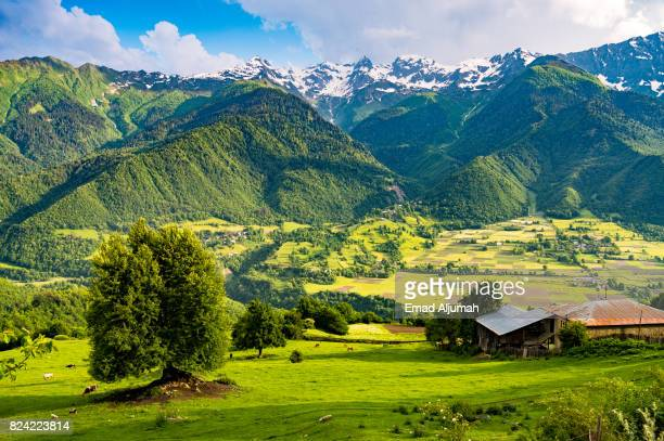 Farms in Mestia village in Svaneti region of Georgia with the Caucasus mountains in the bcakground - June 28, 2017