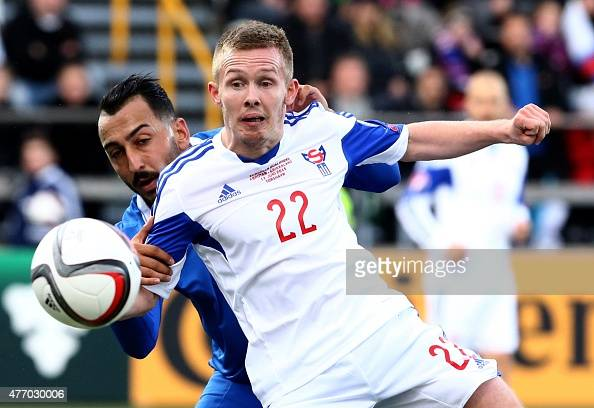 Faroe Island's Bardur Hansen fights for the ball with Greece's Kostas Mitroglou during the UEFA Euro 2016 group F qualifying football match between...