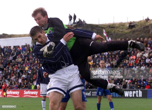 Faroe Islands goalkeeper Jens Martin Knudsen tangles with Scotland's Scott Dobie during the Euro 2004 qualifier in Toftir