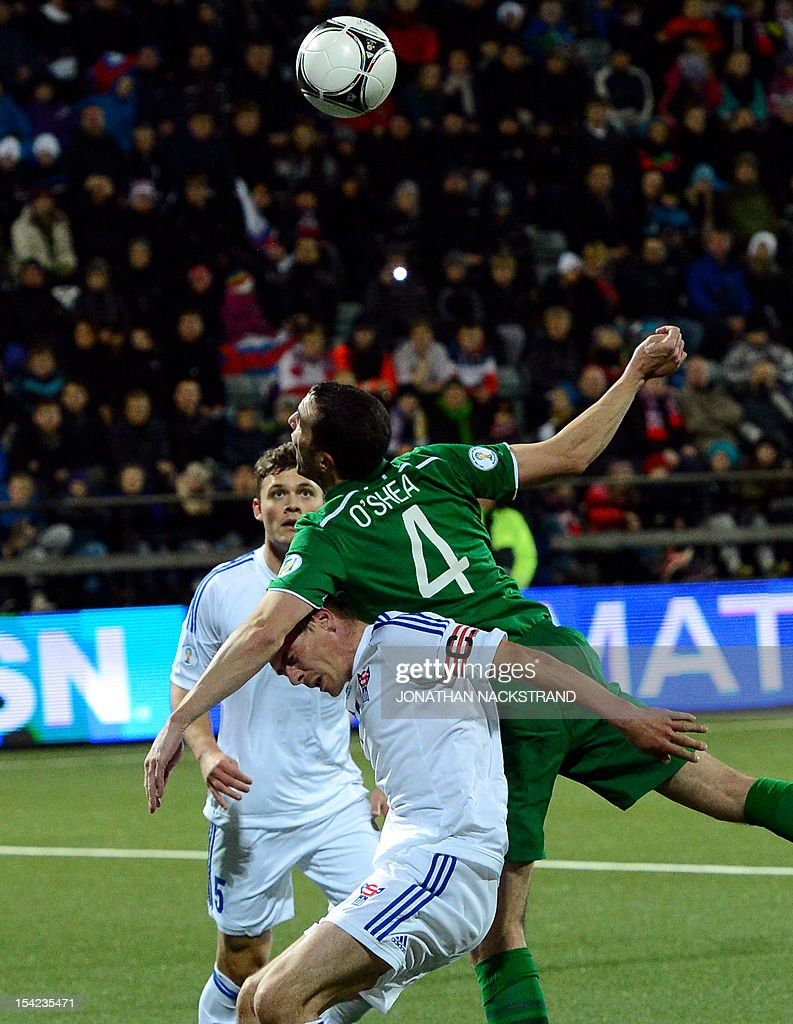 Faroe Islands's national team captain Frodi Benjaminsen and Ireland's John O'Shea (top) vie for the ball during the FIFA 2014 World Cup group C qualifying football match Faroe Islands vs Republic of Ireland at the Torsvollur stadium in Torshavn on October 16, 2012.