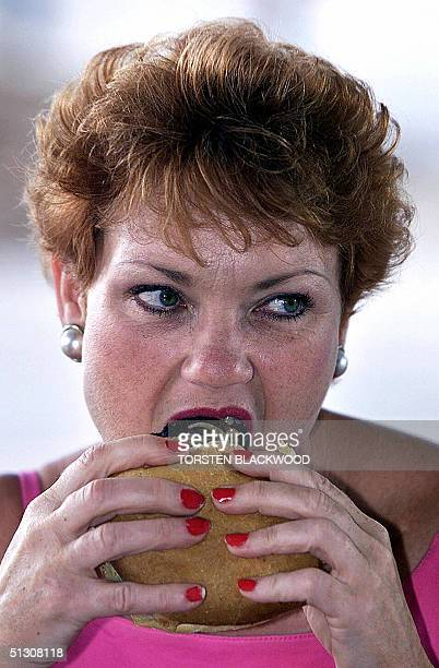 Farright antiimmigration advocate and former MP Pauline Hanson devours a hamburger after voting in the hinterland town of Jimboomba 17 February 2001...