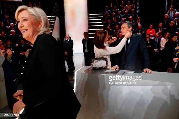Farright Front National party Marine Le Pen smiles as rightwing Les Republicains party Francois Fillon receives make up before a debate organised by...