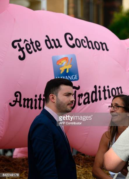 Farright National Front party mayor of Hayange Fabien Engelmann stands by a giant inflatable pig with the inscription 'Friendship and Tradition'...