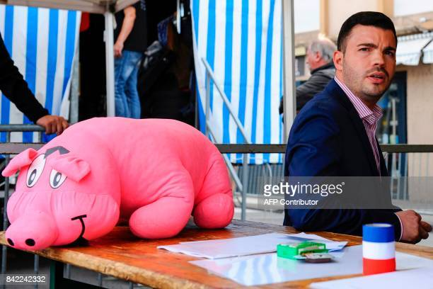 Farright National Front party mayor of Hayange Fabien Engelmann is pictured next to a pig toy as he attends the party's 'Pig Fest' or 'La fete du...
